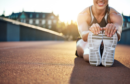 limbering: Woman athlete grabs her shoes as she stretches and smiles while seated on jogging path Stock Photo