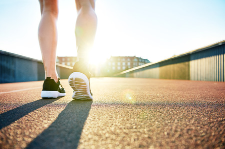 recedes: Low angle view of bare legs wearing running shoes facing apartments as the sun recedes behind them