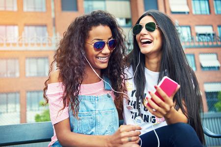 escuchando musica: amigos jovenes hermosas en la ciudad de risa al escuchar o ver algo de humor en su teléfono celular