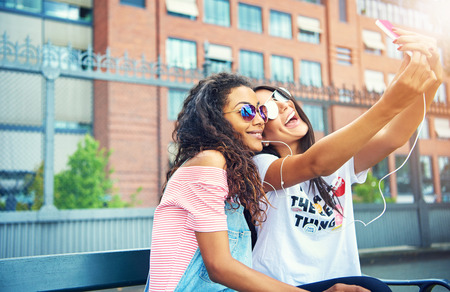 short sleeved: Cute young female friends in sunglasses and short sleeved shirts taking selfies on bench near large brick building