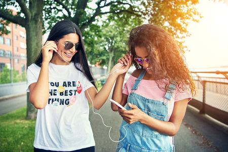 escucha activa: Dos amigas escuchar música en un dispositivo mediante el intercambio de auriculares en una tarde de verano brillante Foto de archivo