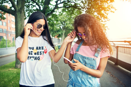 Two female friends listen to music on one device by sharing ear buds on a bright summer afternoon