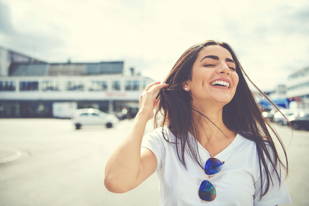 Cute woman with sunglasses on shirt adjusts her long brown hair as it waves in air at large parking lot outdoors Banque d'images