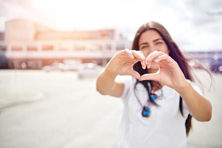 Vrij romantische jonge vrouw die een hartteken met haar vingers maken aangezien zij zich in de hete de zomerzon bevindt in stad