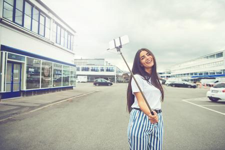 Gelukkige vrouw met lang haar en gestreepte blauwe en witte broek nemen een zelfportret met behulp van een slimme telefoon bevestigd aan een lange paal bekend als selfie stick in het midden van de straat Stockfoto