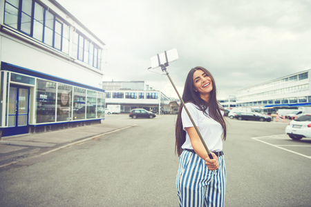 Happy woman with long hair and striped blue and white pants taking a self portrait using a smart phone attached to a long pole known as selfie stick in the middle of street Stock Photo
