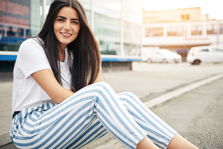 Beautiful woman wearing striped pants smiles at the camera as sunlight strikes nearby building
