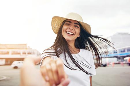 밀 짚 모자를 입고 흰색 셔츠에 웃는 여자는 카메라를 향해 손을 뻗어