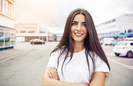 contented: Happy beautiful young adult woman with folded arms and confident expression and long brown hair standing outside in the middle of street Stock Photo