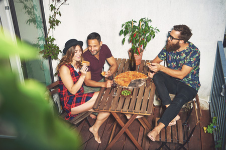 merrymaking: Woman in checkered dress and hat eating pizza on her small apartment porch with two male friends Stock Photo