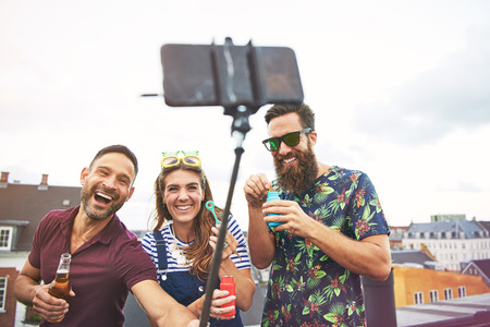 partying: Three partying young adult friends in summer clothing taking pictures of themselves on roof while drinking beer and blowing bubbles
