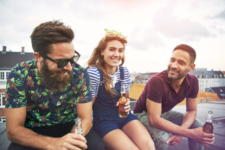 merrymaking: Three happy companions in summer clothing sitting and drinking together on roof in urban setting during summer