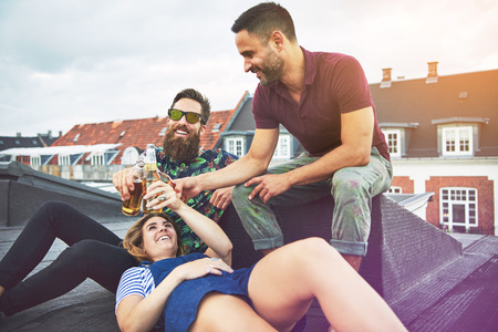 merrymaking: Three young adults enjoying each others company while drinking beer and talking on roof in Europe