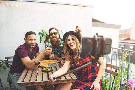 merrymaking: Laughing group of three young adult friends with pizza and wine on table taking selfies