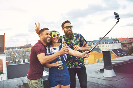 merrymaking: Bearded friend giving rabbit ears to man with beer while woman in sunglasses holds a camera phone at the end of a selfie stick