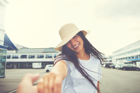 toward: Woman with hat stretches hand toward camera and smiles while standing in parking lot of nearby shopping mall
