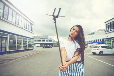 jaunty: Cute woman with long hair and blue striped pants in charming pose taking a self portrait using a smart phone attached to a long pole known as selfie stick in the middle of street