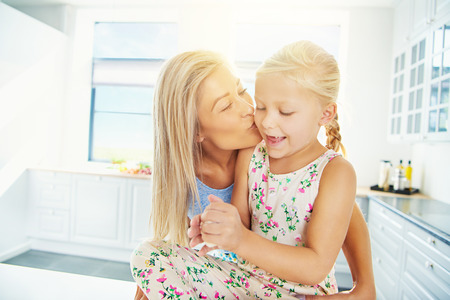 mother kissing daughter: Beautiful young blond mother kissing daughter in ponytails and dress while she plays with bread dough