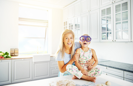 adoring: Bright kitchen scene with copy space of woman holding laughing child in silly purple eyeglasses while seated on table Stock Photo