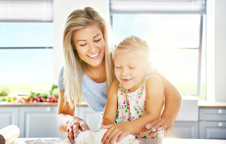 Mother and daughter having fun in the kitchen as the little girl learns to bake helping with kneading the dough