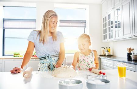 반죽의 마운드에서 작업하는 깨끗한 흰색 부엌 서 베이킹 어머니와 딸은 태양 플레어에 의해 백라이트 함께