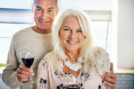 Close up on cheerful attractive European middle aged couple with half full wine glasses in kitchen