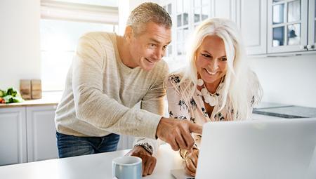 parejas enamoradas: Pares felices con la expresión emocionada mirando el ordenador en cocina con la luz del sol que entraba por la ventana Foto de archivo
