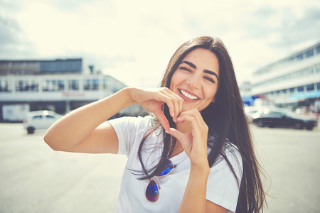 Laughing attractive young woman standing outdoors in an urban environment making a heart gesture with her hands symbolic of love and romance