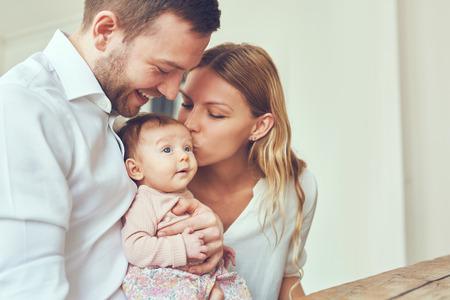 웃는 어머니와 아버지가 집에서 자신의 신생아 딸을 들고