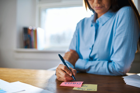 person writing: Selective focus wide angle close up of person writing on pink and yellow sticky notes with marker pen at desk with bright window in background