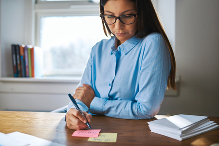 memo pad: Young business woman sitting at her desk making notes on colorful a memo pad in the office with a serious engrossed expression Stock Photo