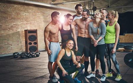 Groep van acht gelukkige gespierde vrouwelijke en mannelijke volwassenen die samen als goede vrienden in de sportschool met grote luidspreker op de achtergrond na een moeilijke training sessie