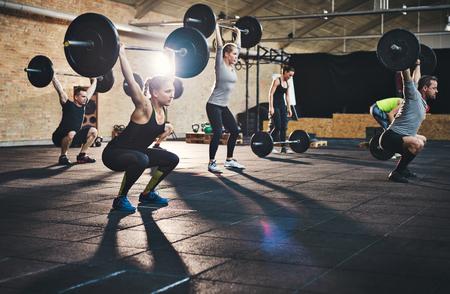 Grupo de jóvenes adultos de sexo masculino muscular y hembras de elevación de grandes pesas en la clase transversal en forma de esteras de espesor y paredes de ladrillo Foto de archivo