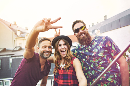 best group: Man makes peace sign beside two smiling friends while they take photo on their apartment patio
