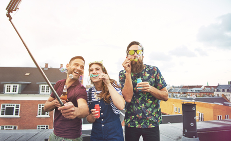 merrymaking: Three drunk friends taking pictures of themselves on roof with camera on selfie stick while blowing bubbles and drinking beer Stock Photo