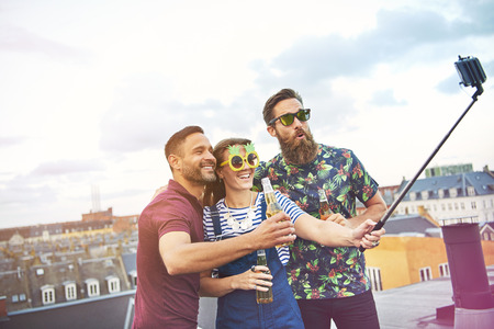 inebriated: Three happy friends with selfie stick taking a picture of themselves while drinking beers on top of roof in city