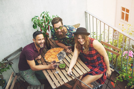 socialising: Woman in checkered dress takes photo with friends on patio while wearing black hat