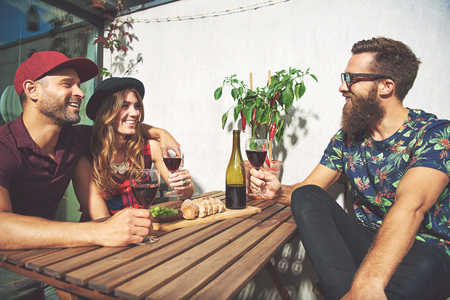 merrymaking: Bearded man with couple drinking wine in summer. Hot red pepper plant and sliced bread are on table.