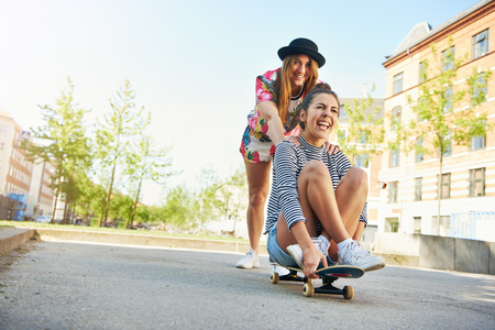 Happy young woman in tie dye clothing and black hat pushing friend on skateboard on road in urban area with apartments surrounding them Stock Photo