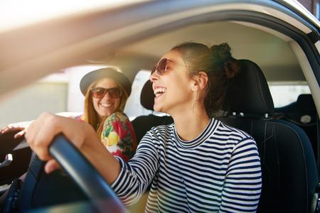 Glimlachende gelukkige jonge vrouw die haar vriend een lift in haar auto in de stad, profiel bekijken door de open zijraam met zon flare Stockfoto
