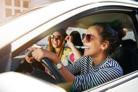 창을 통해 매력적인 젊은 여성의 프로필에 초점을 맞춘 마을에서 차를 여행하는 선글라스 유행 젊은 여자 친구를 웃고