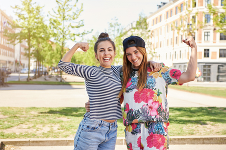 vivacious: Cute vivacious young women friends standing arm in arm on a hot summer day in an urban street waving at the camera