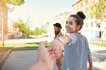 Pretty young woman pulling a man along by the hand turning to look back at him with a happy smile as her friend waits in the background Фото со стока - 62819651
