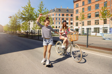 young friends: Pair of cute female friends with excited expressions outside on paved street in city