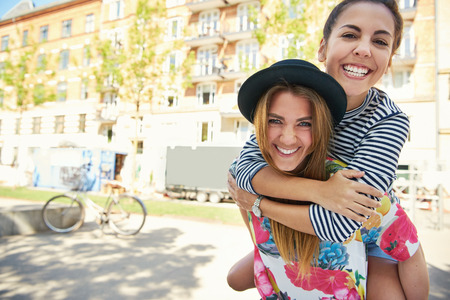 cute girlfriends: Pair of cute girlfriends in striped and flowery shirts holding each other on back outside as if to pose for a photograph