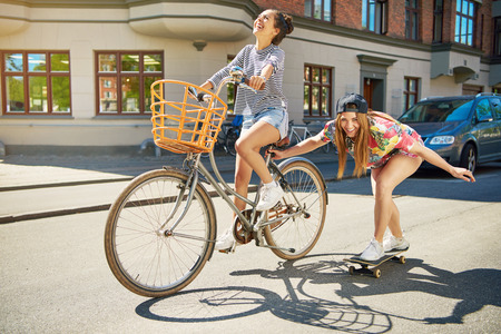 towed: Laughing trendy young woman on a skateboard being towed along an urban street by her friend riding a bicycle