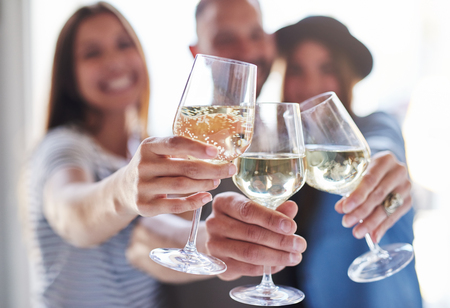 Close up on hands holding toasting wine glasses with out of focus group of three people in back