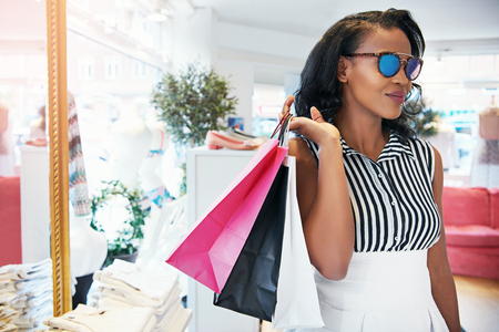 chic woman: Chic elegant young African woman out shopping standing in a clothing store with her purchases in bags over her shoulder wearing trendy sunglasses