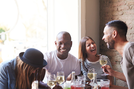 jesting: Joyful group of young adults drunk from wine laughing while seated at dinner table with bright window and brick wall in background