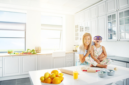 mirth: Adorable mother and daughter in floral patterned dress and purple eyeglasses laughing together in kitchen with bright white walls and windows